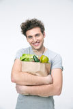 Smiling man holding a bag full of groceries. Over gray background Royalty Free Stock Photography