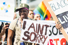 Smiling man holding a banner with strong motto during Stockholm Pride Parade Royalty Free Stock Photography