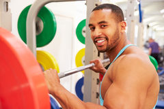 Smiling man holding barbells on a rack at a gym Stock Images