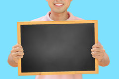 Smiling man holding blank blackboard Stock Photography