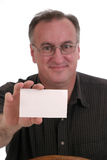 Smiling Man Holding Blank Card. Smiling man wearing glasses holding blank white card suitable for text; focus is on card; isolated on white stock image