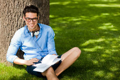 Smiling man holding a book and smiling o the grass Royalty Free Stock Photos