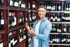 Smiling man holding bottle of wine Stock Photography