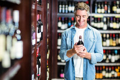 Smiling man holding bottle of wine Stock Images