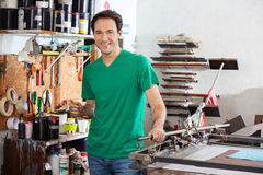 Smiling Man Holding Brush In Paper Factory Stock Photos