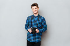 Smiling man holding camera in hands. Young cute man holding camera in hands and smiling over grey royalty free stock photography