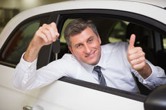 Smiling man holding a car key giving thumbs up Royalty Free Stock Photography