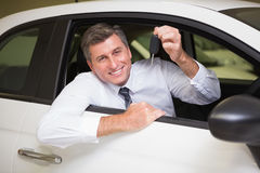 Smiling man holding a car key sitting in his car Royalty Free Stock Photography