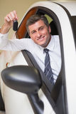 Smiling man holding a car key sitting in his car Stock Images