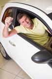 Smiling man holding a car key sitting in his car Royalty Free Stock Photo