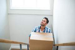 Smiling man holding cardboard box while climbing steps Stock Photography