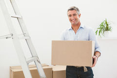 Smiling man holding cardboard box next a stepladder Stock Photos