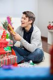 Smiling Man Holding Christmas Presents At Home Stock Images