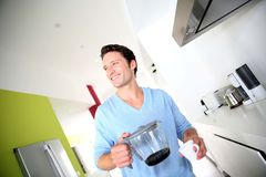 Smiling man holding coffee pot Stock Photography