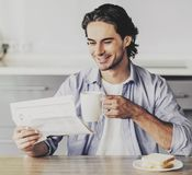 Smiling Man Holding a Cup and Reading Newspaper. Stock Image