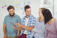 Smiling man holding digital tablet standing with coworkers Stock Photos