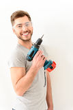 Smiling man holding drill raising up Royalty Free Stock Photo