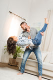 Smiling man holding excited woman in his arms at home Royalty Free Stock Photo
