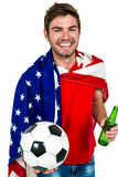 Smiling man holding football and beer bottle wearing American flag Royalty Free Stock Images