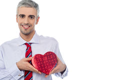 Smiling man holding a gift box. Senior man holding heart shaped gift box Royalty Free Stock Photography