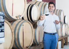 Smiling man holding glass of red wine in shop with woods Stock Photography