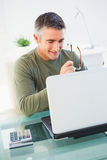 Smiling man holding glasses and using laptop Royalty Free Stock Photography