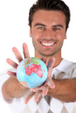 Smiling man holding globe Royalty Free Stock Photo