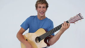 Smiling man holding his acoustic guitar Royalty Free Stock Photography