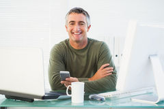 Smiling man holding his mobile phone Royalty Free Stock Photo