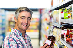 Smiling man holding jar Royalty Free Stock Photography