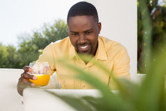 Smiling man holding juice glass while looking at laptop. Smiling young man holding juice glass while looking at laptop in cafe Royalty Free Stock Photography