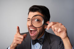 Smiling man holding magnifier near eye and. Funny picture of positive casual young man wearing jacket and bow tie. Man smiling, holding magnifier near eye and royalty free stock image