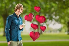Smiling man holding mobile phone against digitally generated red hearts Royalty Free Stock Images