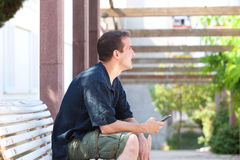 Smiling man holding mobile phone and looking away Stock Photos