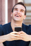 Smiling man holding mobile phone and looking up Stock Photo