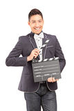 A smiling man holding a movie clap Stock Photography