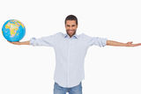 Smiling man holding out a globe and other arm outstretched Stock Images