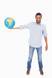 Smiling man holding out a globe Stock Photo