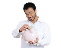 A smiling man holding piggy bank depositing money Stock Photography