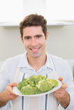 Smiling man holding a plate of broccoli in kitchen Royalty Free Stock Images