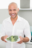 Smiling man holding a plate of broccoli Stock Photos
