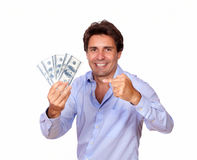 Smiling man holding and pointing cash dollars Royalty Free Stock Images
