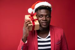 Smiling man is holding present near ear royalty free stock photo