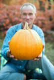 Smiling man holding a pumpkin in his hands Royalty Free Stock Photos