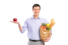 Smiling man holding a red apple and a bag Royalty Free Stock Image