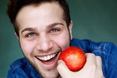 Smiling man holding red apple Royalty Free Stock Photography