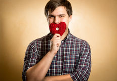 Smiling man holding red heart at mouth Stock Photography