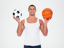 Smiling man holding soccer and basketball ball Royalty Free Stock Images