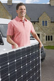 Smiling man holding solar panel Stock Photography