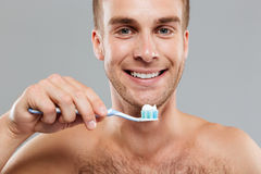 Smiling man holding toothbrush with toothpaste and cleaning his teeth. Smiling young man holding toothbrush with toothpaste and cleaning his teeth over grey Royalty Free Stock Photos